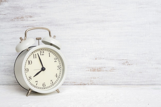 Vintage classic white alarm clock on white grunge background