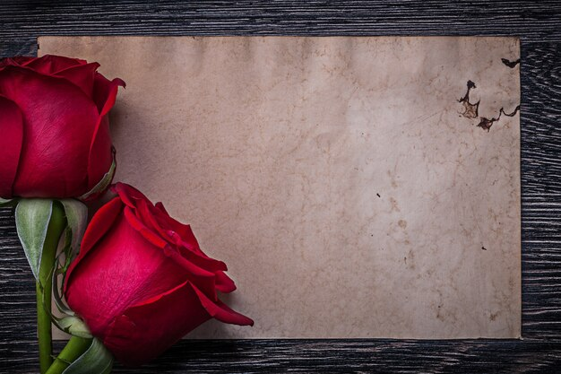 Vintage clean paper red natural roses on wooden board