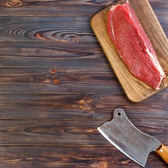 Vintage cleaver and raw beef steak on dark wooden background. copy space