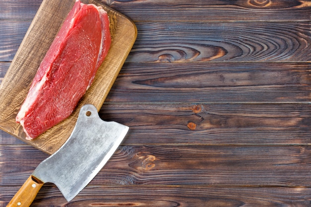 Vintage cleaver and raw beef steak on dark wooden background. copy space