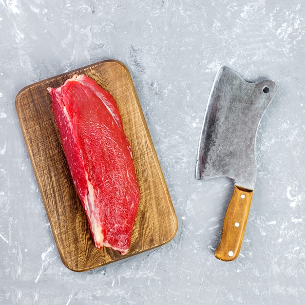 Vintage cleaver and raw beef steak on gray concrete background.