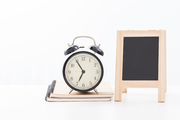Vintage clock and blank blackboard. time at five minute to seven o'clock