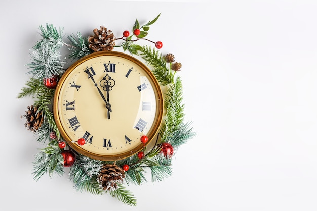 Vintage clock in a christmas decor on a white wall, twelve o'clock, new year's eve