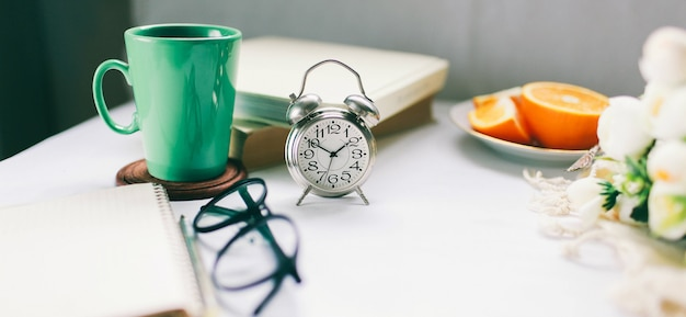 Vintage clock on a desk with a cup of hot coffee and fresh fruit