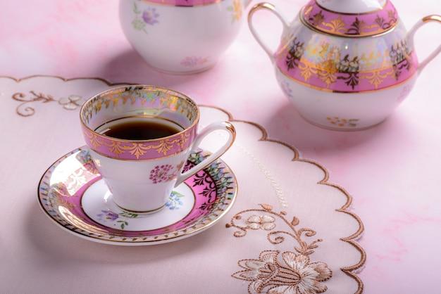 Винтажная кофейная чашка над розовым мрамором