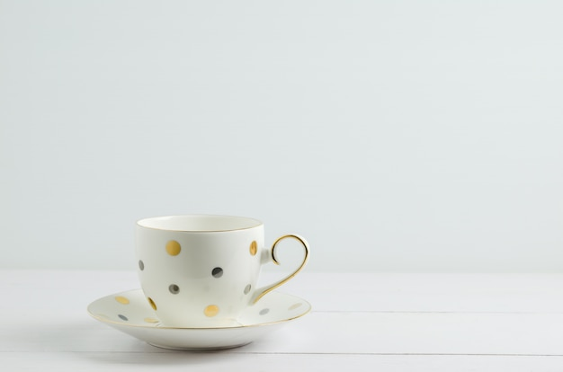 Vintage coffee cup with cute dot on white wooden background