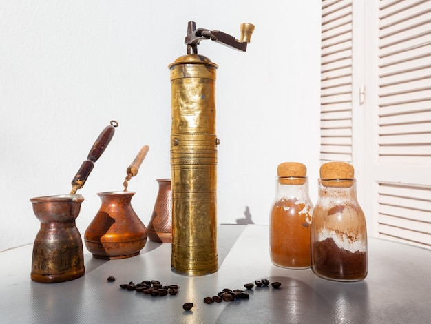 ヴィンテージのコーヒーグラインダーが3つの銅製のジェズヴェの前に立っており、ガラス製のフラスコに挽いたコーヒーが入っています