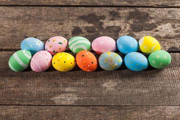 Винтажные красочные пасхальные яйца на фоне деревянного стола