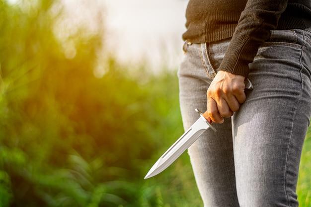 Vintage combat knife bayonet in women's hand.
