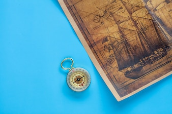Vintage Compass and old sea map on color background.