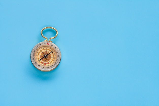 Vintage compass on color background