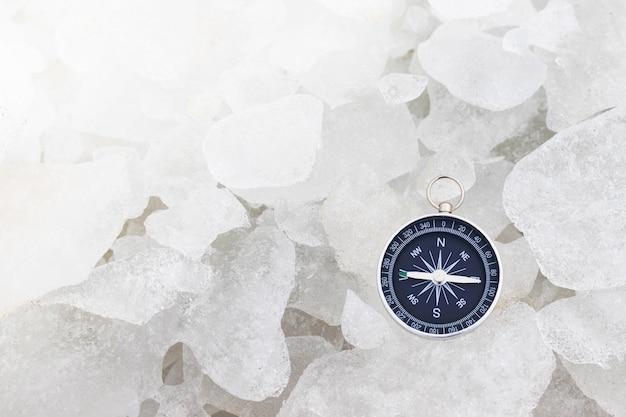 얼음 표면에 누워 빈티지 나침반입니다. 겨울 날 하이킹 여행자 장비. 모험과 발견 테마. 여행을위한 내비게이션.