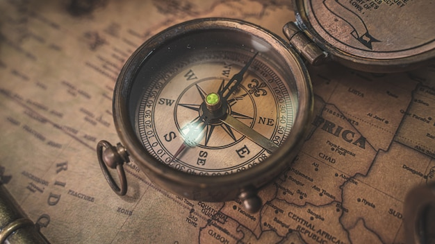 Vintage compass on old world map