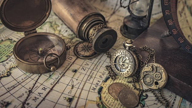 Vintage compass, watch pendant and telescope on old world map