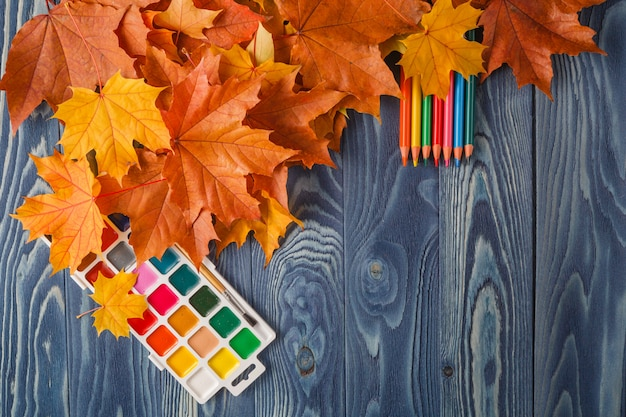 Vintage composition with autumn leaves on wooden background