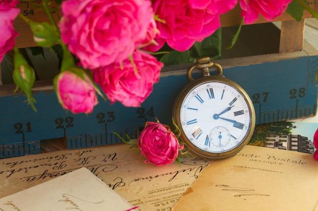 꽃과 골동품 시계와 함께 오래 된 편지의 빈티지 개념 더미