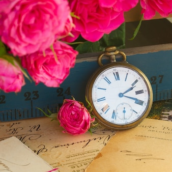 Vintage concept  pile of old letters  with flowers and  antique  clock