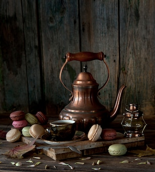 Vintage copper coffee pot, cup of black coffee and colorful macaroons on rustic wooden background.