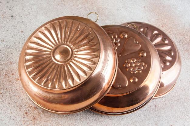Vintage copper molds on a concrete background.