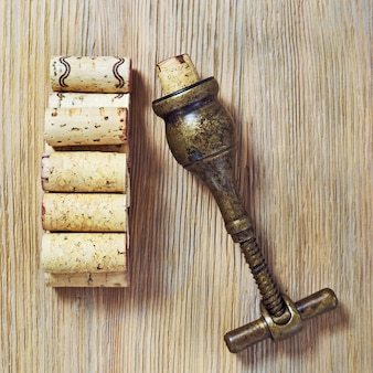 Vintage corkscrew and heap used wine corks on wooden background.