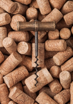 Vintage corkscrew on top of various wine corks. macro