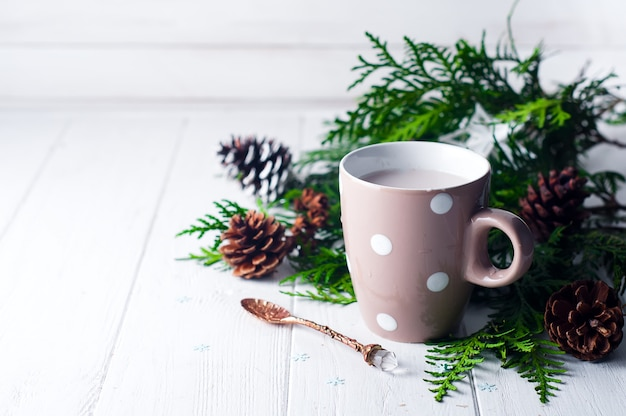 Vintage cup of hot cocoa on wooden background decorated with spruce and pine cones