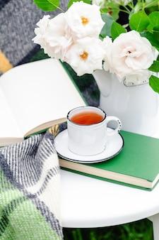 Vintage cup of tea near open book flowers in garden. romantic leisure breakfast