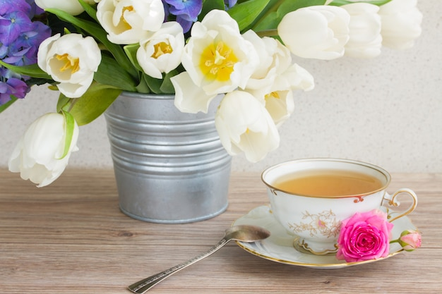 Vintage cup of tea with white tulips