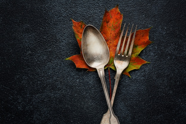 Vintage cutlery with autumn leaves on dark surface