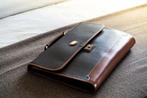 Vintage dark leather handbag on brown  background