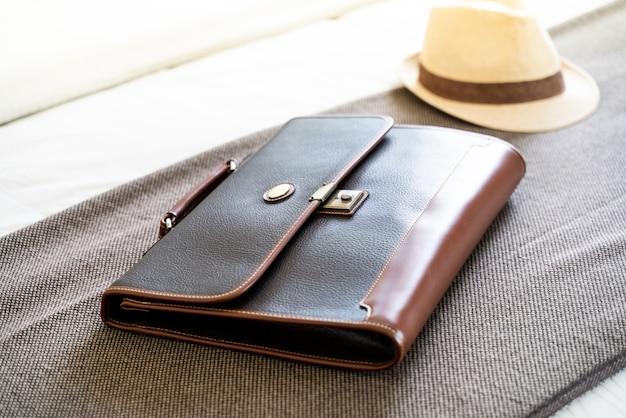 Vintage dark leather handbag on brown and hat weave background