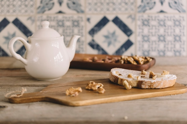 Vintage decoration with nuts on wooden board and tea pot