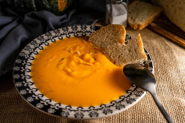 田舎のカボチャとニンジンのクリームスープ、または黄麻布の素朴な雰囲気のヴィンテージディーププレート