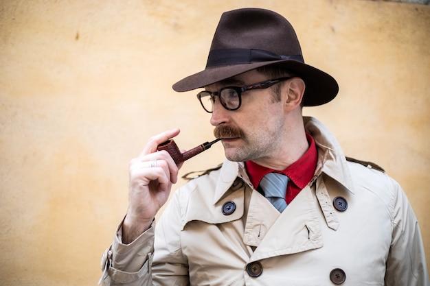 Винтажный детектив курит трубку на улице в безобразной обстановке