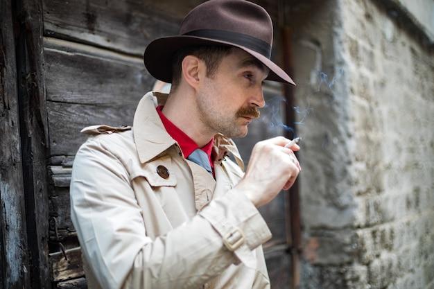Vintage detective smoking a sigarette ina city slum