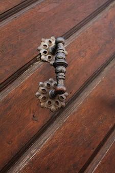 茶色の木製ドアのヴィンテージドアハンドル。クローズアップショット