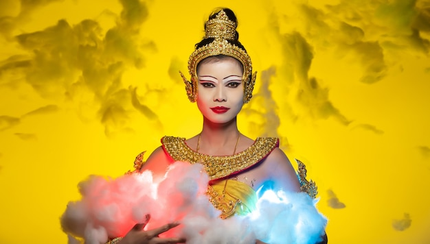 Vintage dress of thai, cambodia, myanmar traditional costume or ancient asia gold cloth for goddess in asian beautiful woman hold blue red cloud