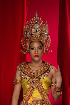 Vintage dress of thai, cambodia, myanmar traditional costume or ancient asia gold cloth for goddess in asian beautiful woman with decorative crown necklace