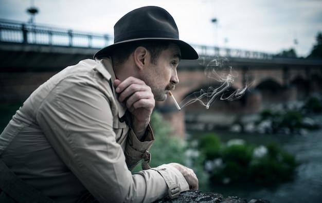 Винтаж одетый мужчина курит сигарету возле старого моста