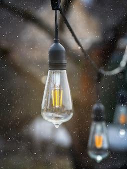 雪の中で屋外のヴィンテージエジソンタイプの白熱灯。垂直方向のビュー。