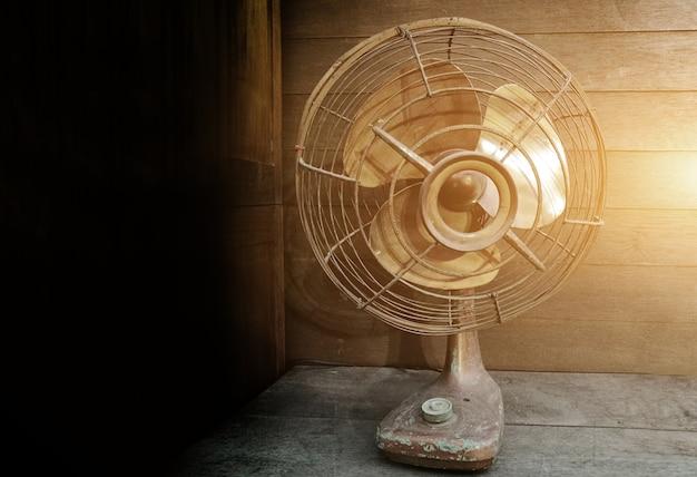 Vintage electric fan on old wood background