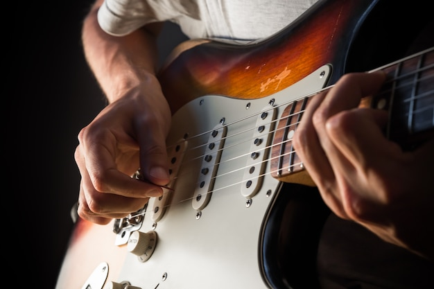 Vintage electric guitar closeup, male hands playing with a pick