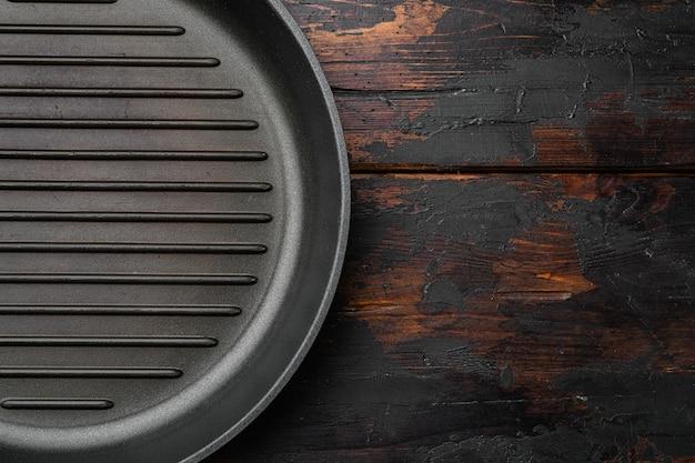 Винтажная пустая сковорода для гриля с копией пространства для текста или еды с копией пространства для текста или еды, плоская планировка, вид сверху, на фоне старого темного деревянного стола