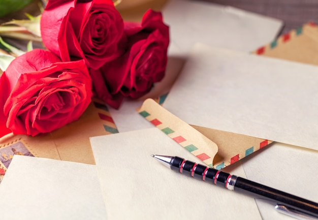 Vintage envelopes, red rose and sheets of paper scattered on the wooden table for writing romantic letters.