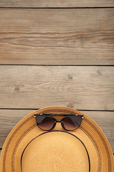 Vintage fabricate straw hat and sunglasses on grey wooden background.