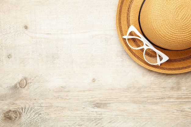 Vintage fabricate straw hat and sunglasses on light background.