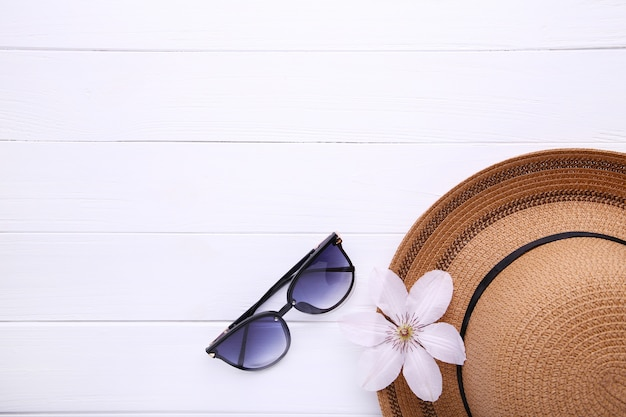 Vintage fabricate straw hat and sunglasses on white.