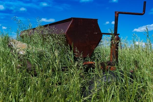 カナダのサスカチュワンにある高い芝生に囲まれたフィールドでのヴィンテージ農業用ディスクハロー