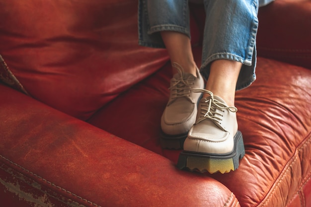 Винтажная мода, женские ножки в джинсовых джинсах и городские кроссовки на фоне красного старого кресла в стиле ретро, фото крупным планом
