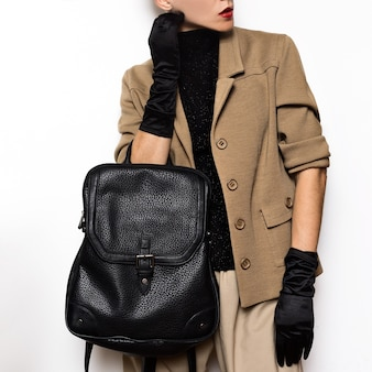 Vintage fashion female student beige classic costume and stylish accessories. red lipstick, gloves. backpack mix trends and vintage outfit